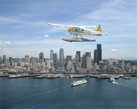 Seaplane flys over harbor and office buildings